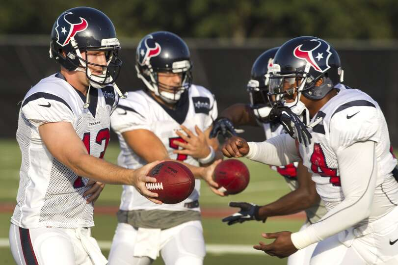 Quarterback T.J. Yates (13) hands the ball off to running back Ben Tate (44).