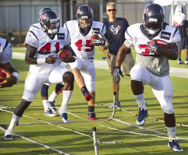 Running back Cierre Wood (41), fullback Zach Boren (45) and running back Deji Karim (39) run through