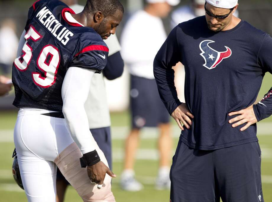 Outside linebacker Whitney Mercilus points to his thigh while talking to assistant linebackers coach Bobby King. Mercilus strained his hamstring during Monday's practice. Photo: Brett Coomer, Chronicle
