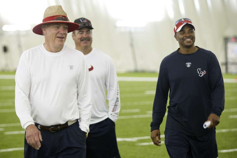 Owner Bob McNair, left, walks off the field with Cal McNair, Texans COO, and general manager Rick Sm