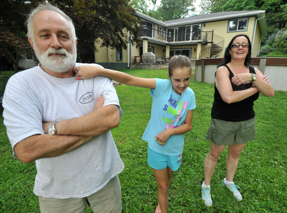 Siobhain Duggan, 10, center tries to get her father, Jim, to smile as her mother, Pat, looks on outside their home in Stamford on Monday, July 29, 2013. Photo: Jason Rearick / Stamford Advocate