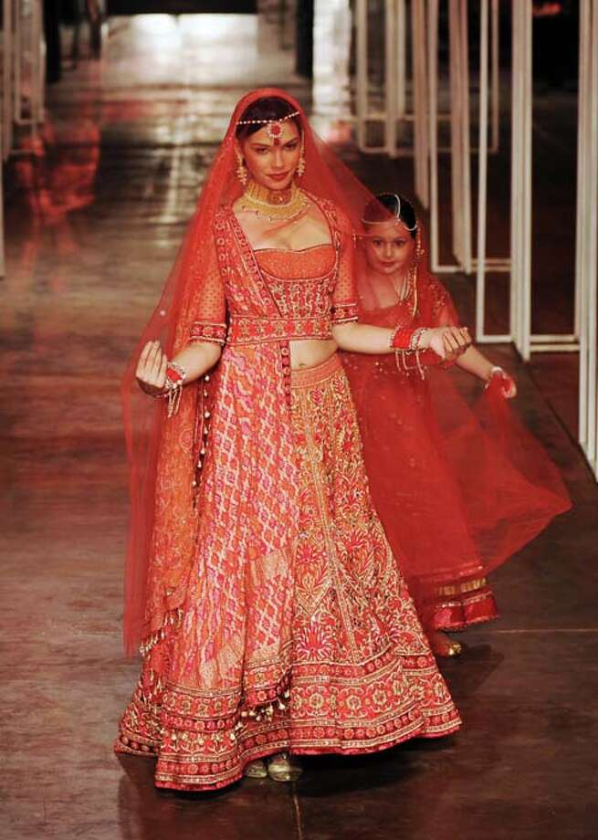 Models present creations by Tarun Tahiliani during the Grand Finale of Indian Bridal Fashion Week in New Delhi on July 28, 2013. AFP PHOTO/ SAJJAD HUSSAIN        (Photo credit should read SAJJAD HUSSAIN/AFP/Getty Images) Photo: SAJJAD HUSSAIN, AFP/Getty Images / 2013 AFP