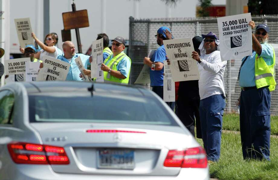 United Airlines employees and Union members hold signs as they line the sidewalk on JFK Blvd on Monday, July 29, 2013, in Houston. Over 100 union and United Airlines' employees came out to protest the airlines plans to outsource work. Photo: J. Patric Schneider, For The Chronicle / © 2013 Houston Chronicle
