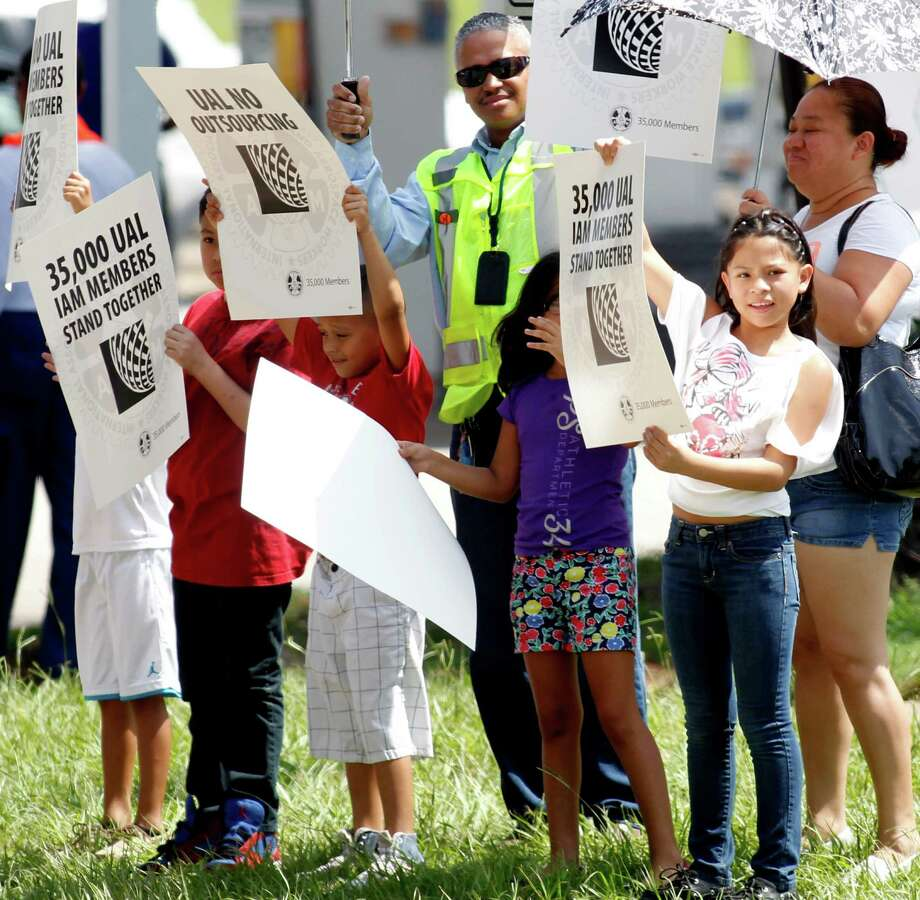 United Airlines employees and family members hold signs as they line the sidewalk on JFK Blvd on Monday, July 29, 2013, in Houston. Over 100 union and United Airlines' employees came out to protest the airlines plans to outsource work. Photo: J. Patric Schneider, For The Chronicle / © 2013 Houston Chronicle