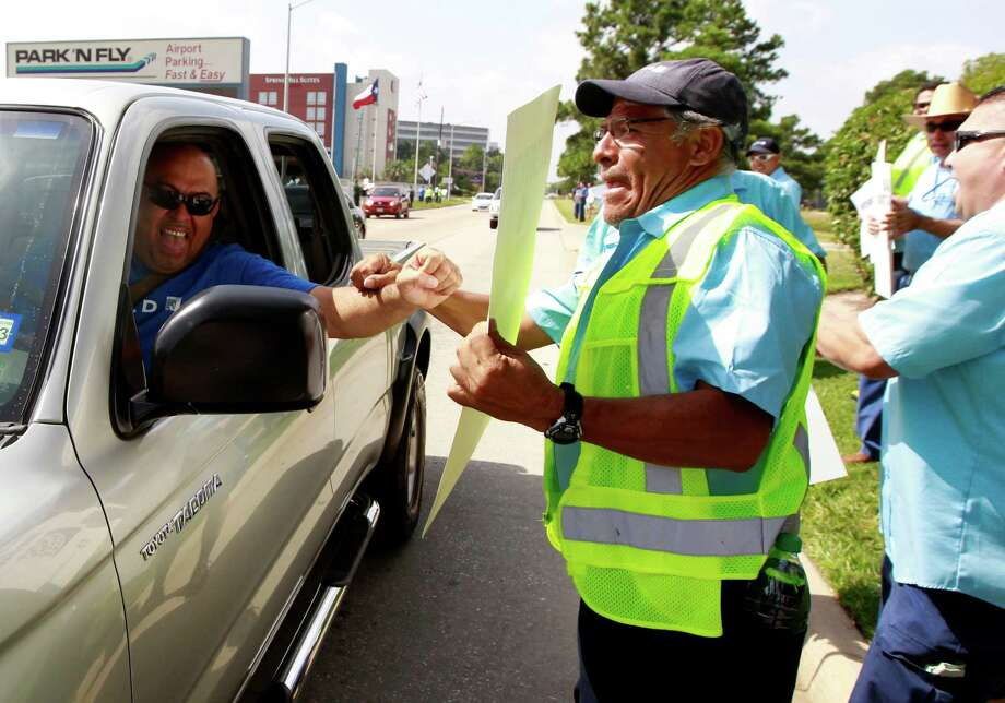 United Airlines ground service employee Hugo Huertas, right, shakes a drivers' hand as he and over a 100 protestors line the sidewalk on JFK Blvd on Monday, July 29, 2013, in Houston. The protestors came out to protest the airlines plans to outsource work. Photo: J. Patric Schneider, For The Chronicle / © 2013 Houston Chronicle