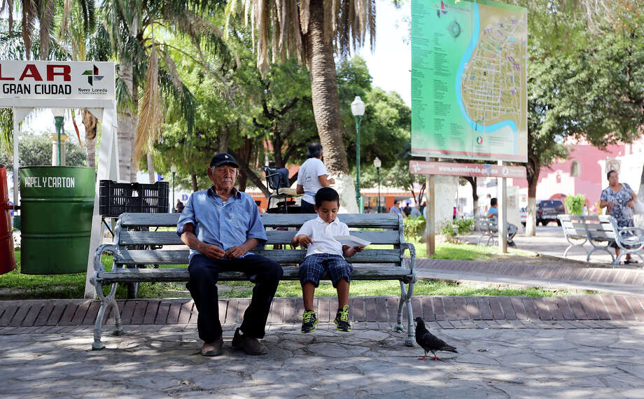 A man and boy have lunch in Plaza Benito Juarez Thursday July 25, 2013 in Nuevo Laredo, Tamaulipas, Mexico. Photo: Edward A. Ornelas, San Antonio Express-News / © 2013 San Antonio Express-News