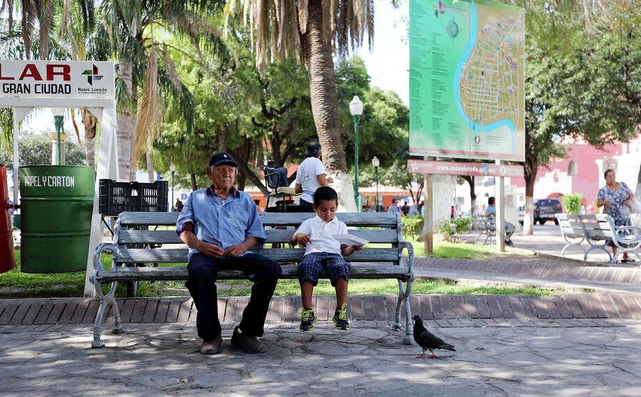 A man and boy have lunch in Plaza Benito Juarez Thursday July 25, 2013 in Nuevo Laredo, Tamaulipas, Mexico. Photo: Edward A. Ornelas, San Antonio Express-News / © 2013 San Antonio Express-News