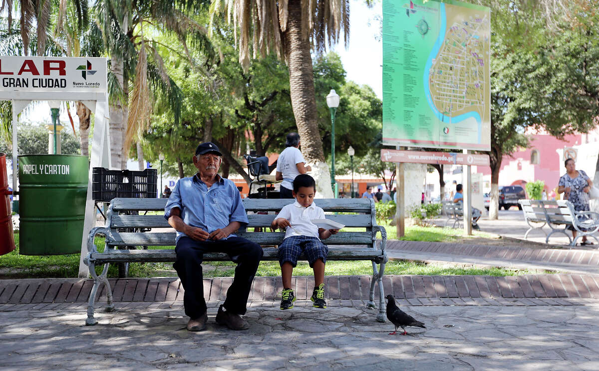 A man and boy have lunch in Plaza Benito Juarez Thursday July 25, 2013 in Nuevo Laredo, Tamaulipas, Mexico.