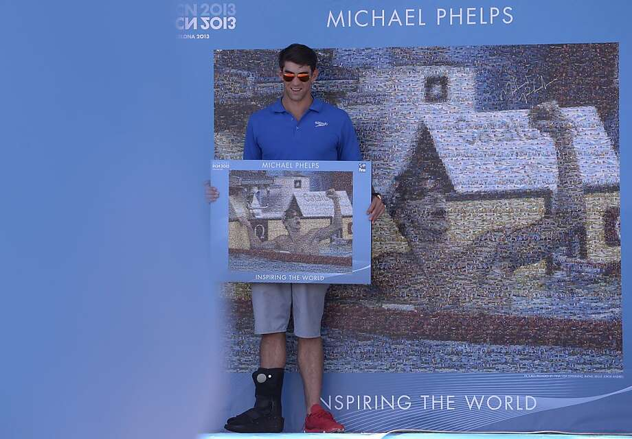 Former Olympic and world swimming champion Michael Phelps of the US unveils a mosaic installed in his honour at the FINA Swimming World Championships in Barcelona, Spain, Sunday, July 28, 2013 .(AP Photo/Manu Fernandez) Photo: Manu Fernandez, Associated Press