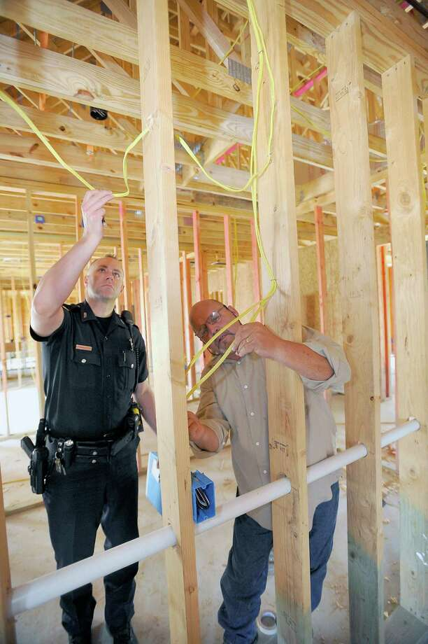 Beaumont Police Officer Stewart Hanley, left, looks over some of the damaged electrical wire with Contractor Tom Neild, right, as the two work on filing out a report. Copper thieves broke into and stole copper wire and some copper tubing from the new Anayat House being built on 14th Street. The project has been a decade in the making and now completion time will be delayed. Dave Ryan/The Enterprise
