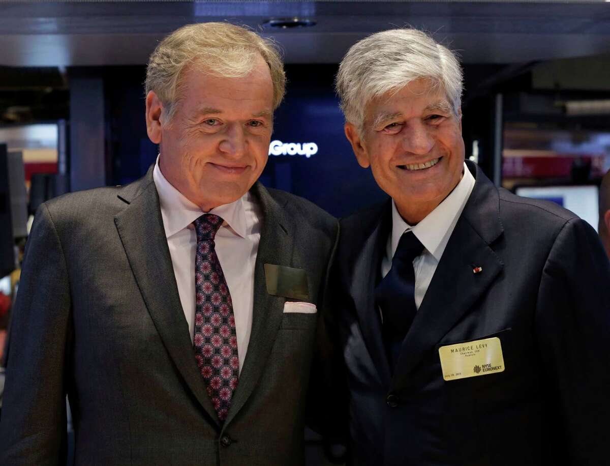 """Omnicom Group President and CEO John Wren, left, and Publicis Groupe Chairman and CEO Maurice Levy pose for photos on the floor of the New York Stock Exchange Monday, July 29, 2013. Omnicom and Publicis say they are combining in a """"merger of equals"""" that will create the world's largest advertising firm, one worth more than $35 billion. (AP Photo/Richard Drew)"""