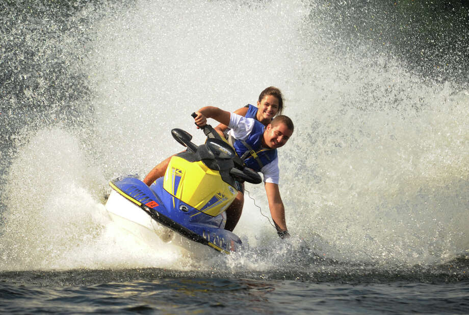Christopher DeFeo, 17, of Bethany, and Lexi Komaromi, 15, of Seymour, take a high speed ride on a personal watercraft on Lake Zoar in Monroe, Conn. on Monday, July 28, 2013. Photo: Brian A. Pounds / Connecticut Post