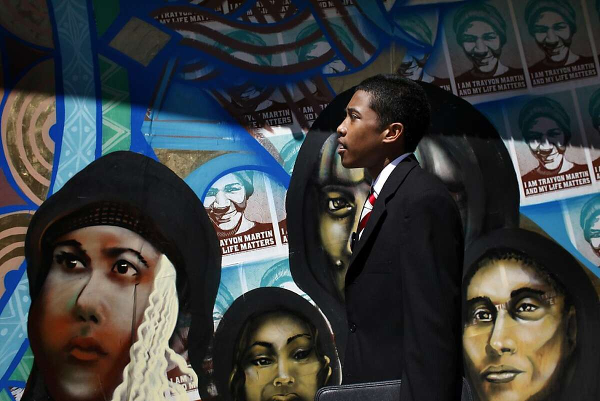 Justin Jones, 17, walks past a mural representing the Oscar Grant's and Trayvon Martin's of the world, Friday July 27, 2013, in downtown Oakland, Calif. The mural was painted on the plywood that covers a window that was shattered during the protests days after the Trayvon Martin verdict. Jones was the organizers of one of the few peaceful protest following the verdict.