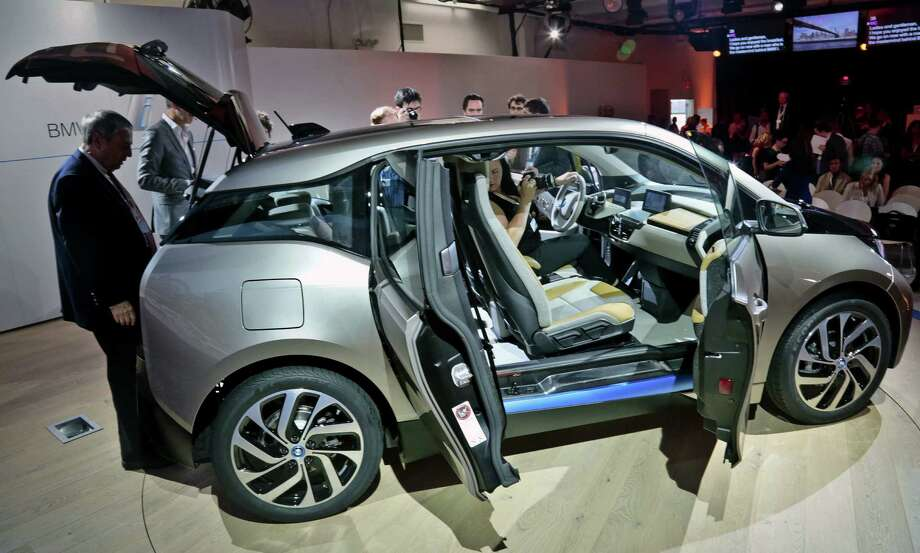 The new BMWi3 electric vehicle is unveiled Monday, marking the automaker's entry into the EV market. Electric vehicles on average cost more than hybrids but offer advantages on down the road because their fuel and maintenance expenses are less. Photo: Bebeto Matthews / Associated Press