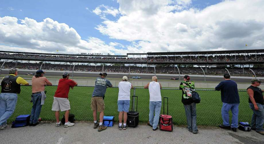Fans watch the running of the Brickyard 400 auto race from the inside of the track at the Indianapolis Motor Speedway in Indianapolis, Sunday, July 28, 2013. (AP Photo/Doug McSchooler) ORG XMIT: NAA122 Photo: Doug McSchooler / FR170771