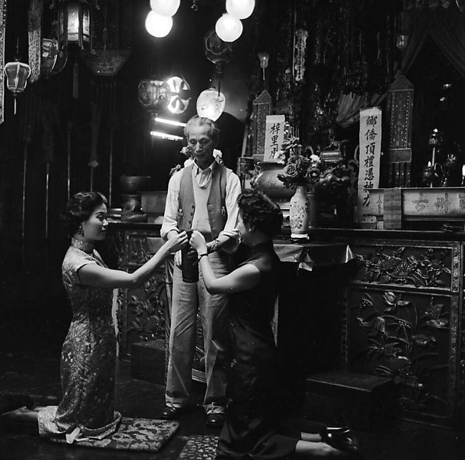 Two Chinese-American women come to have their fortunes told by Chin Toy, an attendant at the Chinese temple or joss house on Pine Street in Chinatown, San Francisco. The temple is owned by the Kong Chow Family Society, and is frequented by followers of Buddhism, Confucianism and Taoism. Photo: Orlando, Getty Images
