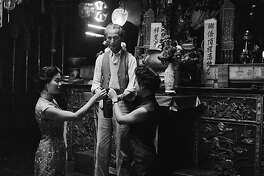 Two Chinese-American women come to have their fortunes told by Chin Toy, an attendant at the Chinese temple or joss house on Pine Street in Chinatown, San Francisco. The temple is owned by the Kong Chow Family Society, and is frequented by followers of Buddhism, Confucianism and Taoism.   (Photo by Orlando/Getty Images)