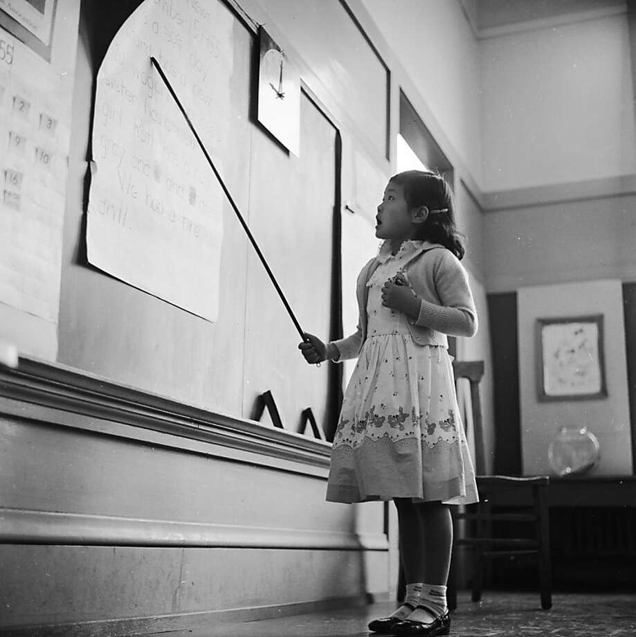 circa 1955:  A little girl reads aloud from the board during an English class at the Commodore Stockton School in Chinatown, San Francisco. The school provides education for most of Chinatown's younger children. Photo: Orlando, Getty Images