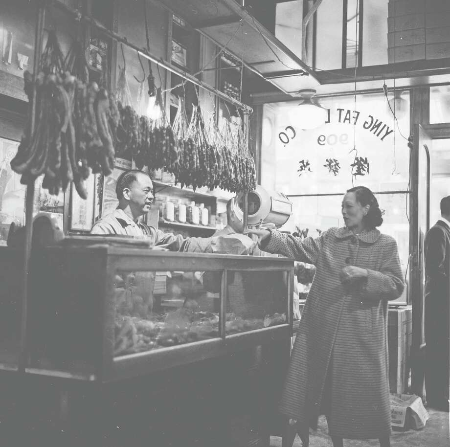 circa 1955:  A customer receives her parcel of meat from the butcher at Ying Fat Lung's Chinese shop in Chinatown, San Francisco. Overhead hang dried bunches of Chinese sausage and bacon. Photo: Orlando / Getty Images / Hulton Archive