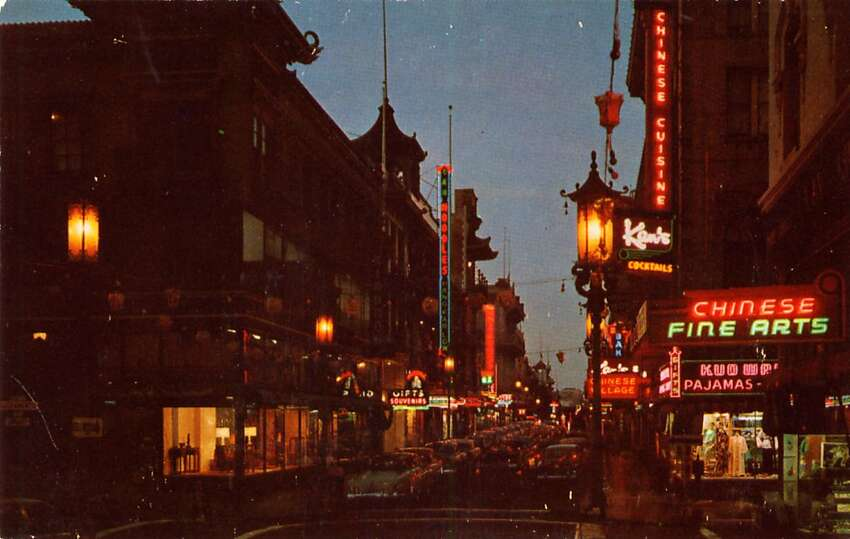 A night view of San Francisco's Chinatown in the 1950's. The streets are crowded with traffic and neon signs light up the night.