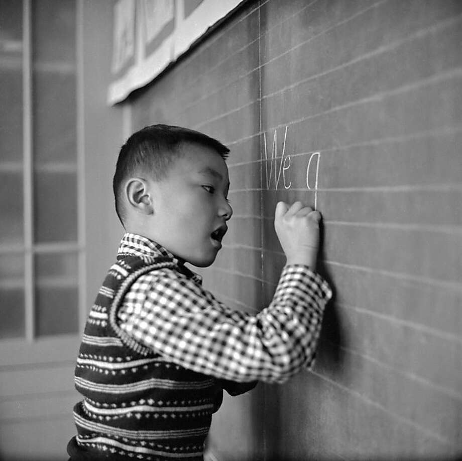 circa 1955:  A little boy writes carefully on the blackboard during an English lesson at the Commodore Stockton School in Chinatown, San Francisco. The school provides education for most of Chinatown's younger children, and was named after Robert F Stockton, the first military governor of California. Photo: Orlando, Getty Images