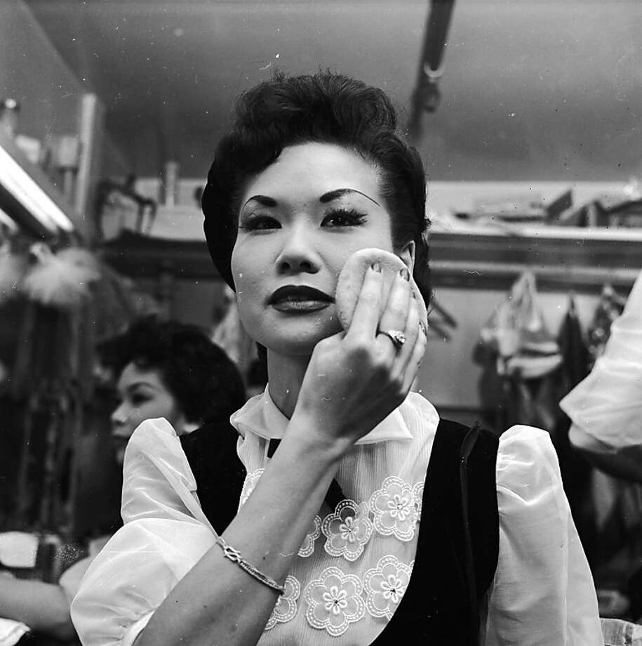 Circa 1955:  Estelle Jung, a chorus girl at the Forbidden City nightclub in Chinatown, San Francisco, adds the finishing touches to her make-up prior to her act. Photo: Orlando, Getty Images