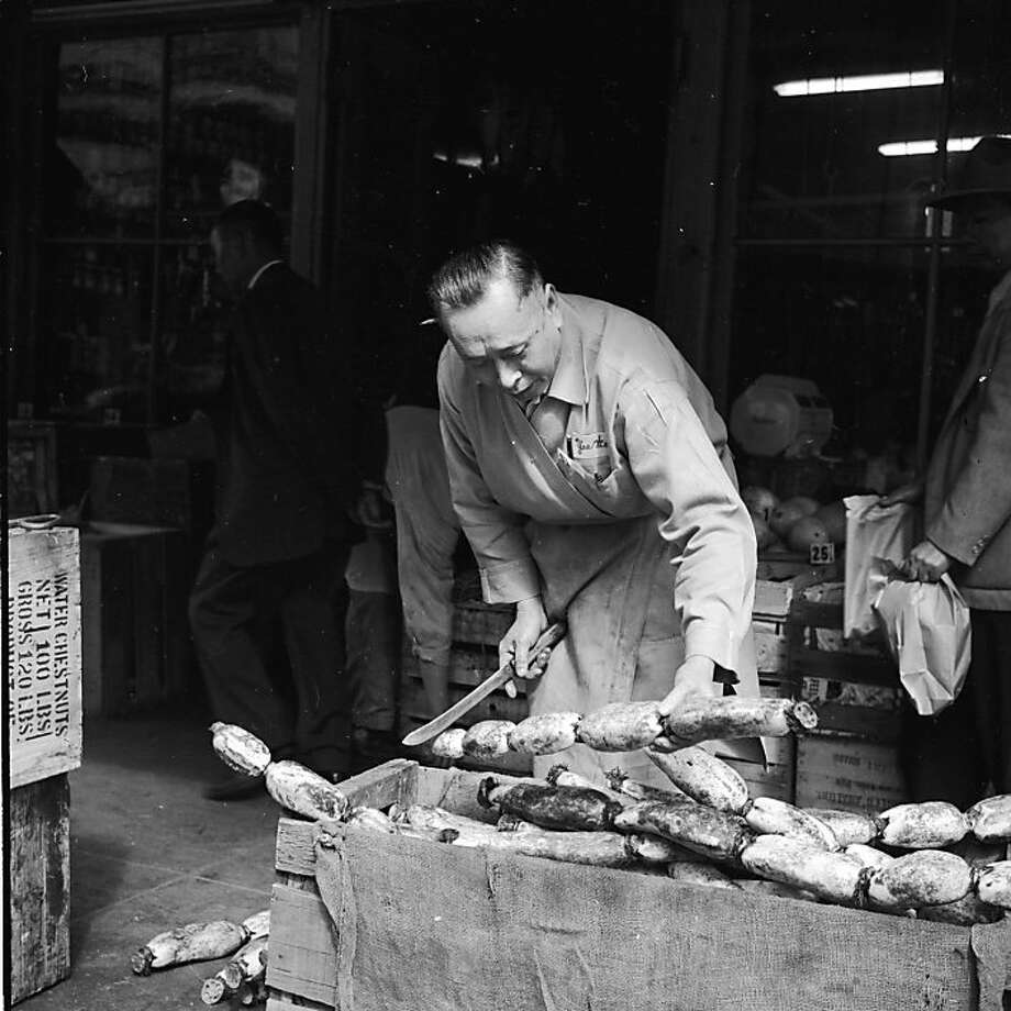 Circa 1955:  A stallholder at the Yee Wo market in Chinatown, San Francisco, slices off a section of lotus root for a customer. The large knobbly root is imported from Hong Kong, and is a popular ingredient in soup. Photo: Orlando, Getty Images