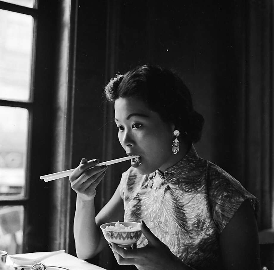 circa 1955:  A young woman eats a bowl of rice using chopsticks in Johnny Kan's famous Chinese restaurant in Chinatown. Photo: Orlando, Getty Images