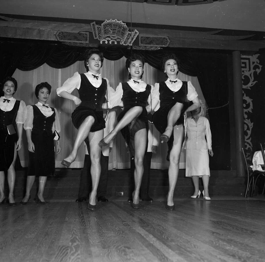 Circa 1955:  A line of Chinese chorus girls entertains visitors to the Forbidden City nightclub in Chinatown. Photo: Orlando, Getty Images