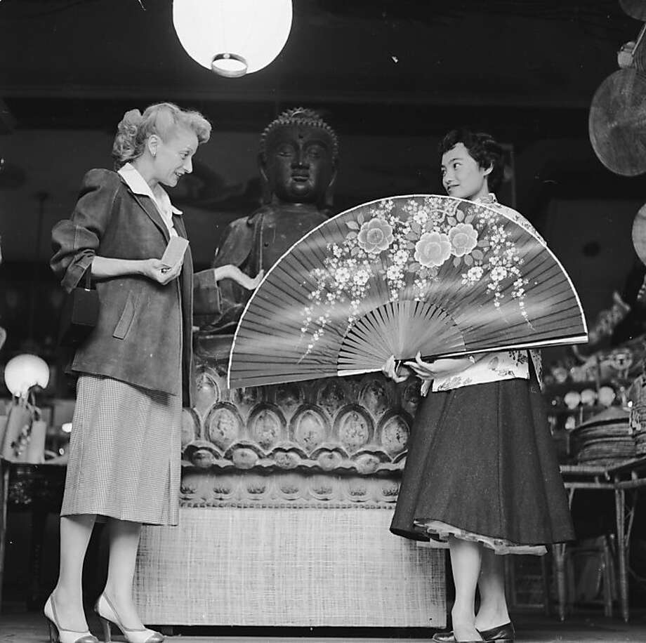 Circa 1955:  A shop assistant at the Tai Ping Company boutique on Grant Avenue, Chinatown, San Francisco, demonstrates a giant Chinese fan to an interested customer. Photo: Orlando, Getty Images