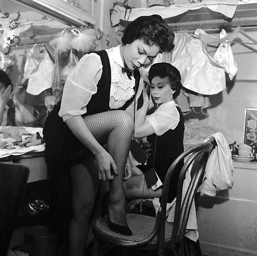 circa 1955: Two chorus girls prepare for their act in the dressing room of the Forbidden City nightclub in Chinatown, San Francisco.