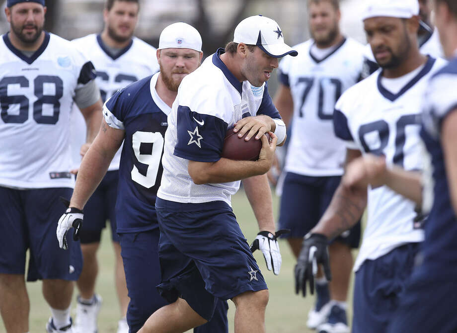 QB Tony Romo, playfully running with the ball at training camp, says he won't play long in the first exhibition game at the Hall of Fame, if he plays at all. Photo: Kin Man Hui / Express-News