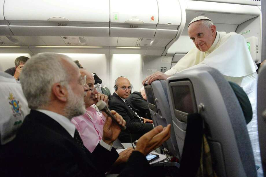 "Pope Francis answers reporters questions during a news conference aboard the papal flight on its way back from Brazil, Monday, July 29, 2013. Pope Francis reached out to gays on Monday, saying he wouldn't judge priests for their sexual orientation in a remarkably open and wide-ranging news conference as he returned from his first foreign trip. ""If someone is gay and he searches for the Lord and has good will, who am I to judge?"" Francis asked. His predecessor, Pope Benedict XVI, signed a document in 2005 that said men with deep-rooted homosexual tendencies should not be priests. Francis was much more conciliatory, saying gay clergymen should be forgiven and their sins forgotten. Francis' remarks came Monday during a plane journey back to the Vatican from his first foreign trip in Brazil. (AP Photo/Luca Zennaro, Pool) ORG XMIT: XVAT101 Photo: Luca Zennaro / ANSA"