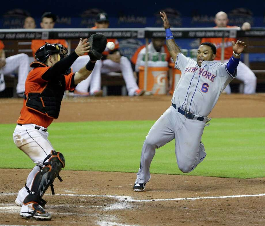 New York Mets' Marlon Byrd (6) slides safely into home plate as Miami Marlins catcher Jeff Mathis attempts the tag during the seventh inning of a baseball game, Monday, July 29, 2013 in Miami. Byrd scored on a double by Ike Davis. (AP Photo/Wilfredo Lee) ORG XMIT: FLWL104 Photo: Wilfredo Lee / AP