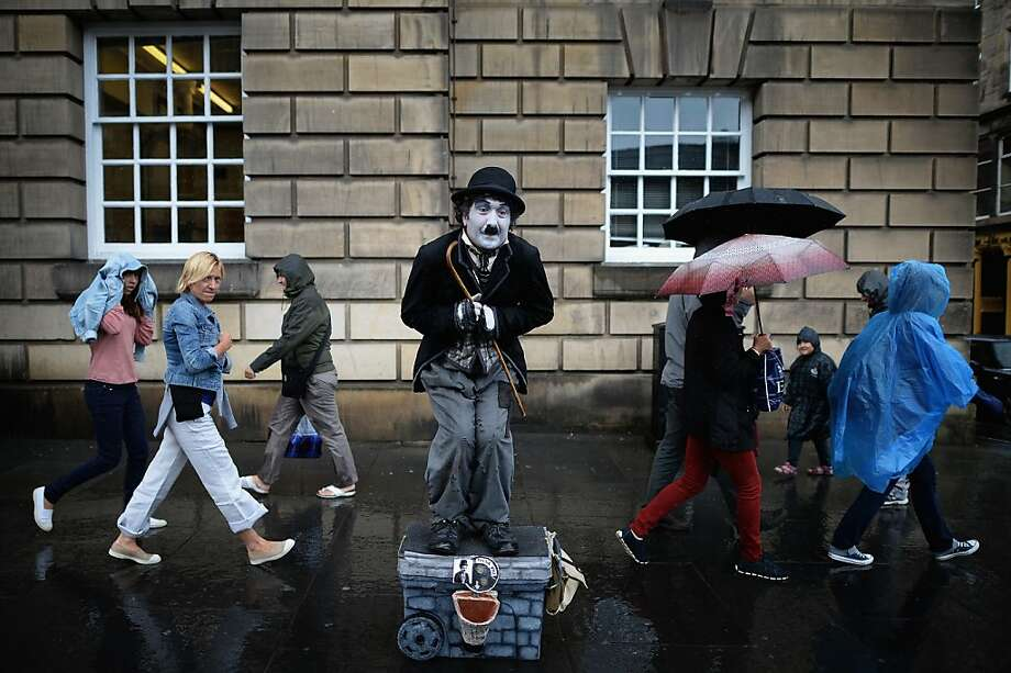 EDINBURGH, SCOTLAND - JULY 29:  Members of the public, walk past a street entertainer on the Royal Mile on July 29, 2013 in Edinburgh, Scotland. The city is preparing ahead of the Edinburgh Fringe Festival which runs from the 2 -26 August and is one of the largest arts festivals in the world, dating back to 1947. The festival attracts thousands of performers from across the world to showcase their acts in Scotland's capital. (Photo by Jeff J Mitchell/Getty Images) *** BESTPIX *** Photo: Jeff J Mitchell, Getty Images