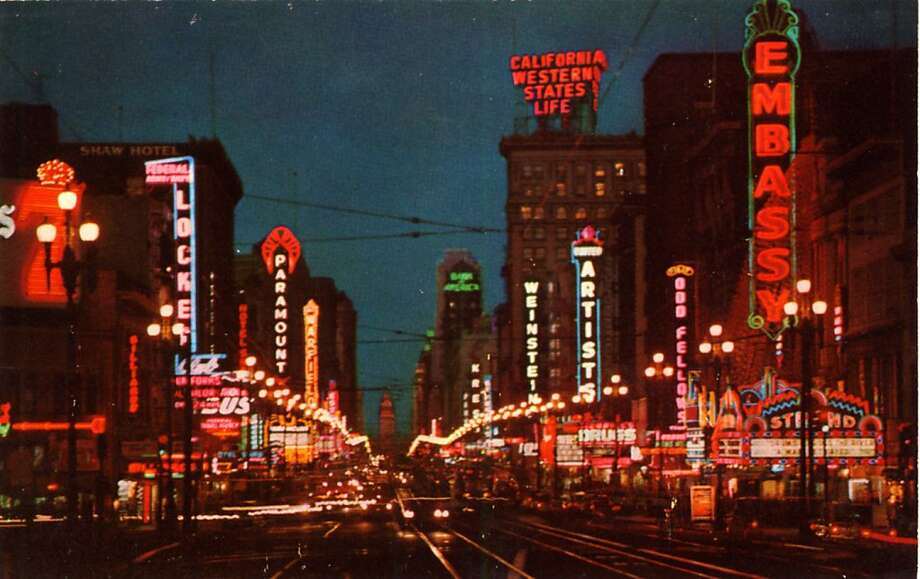 Vintage 1957 postcard showing a night view of market streets with its bright neon lights and busy thoroughfare, the Ferry Building is visible in the distance at the end of Market Street. Photo: Curt Teich Postcard Archives, Getty Images