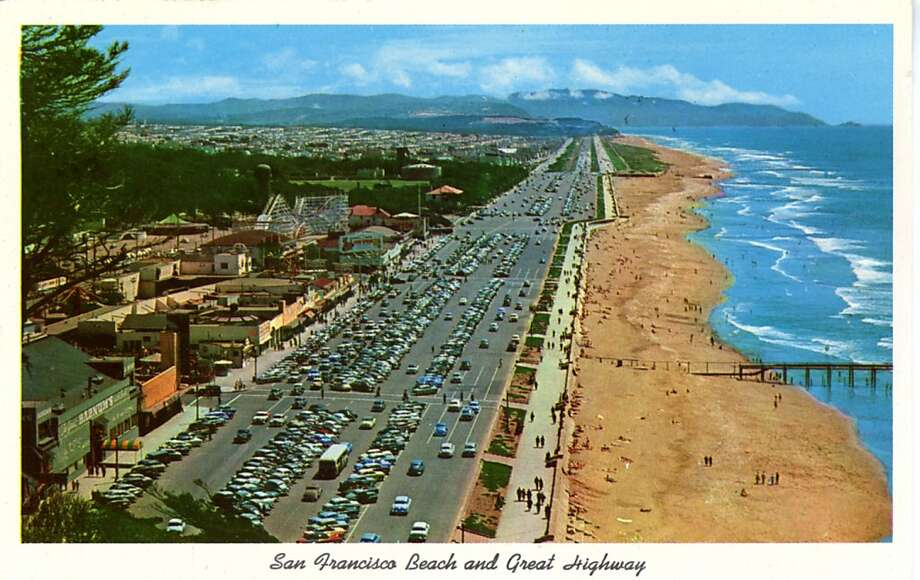 Vintage postcard showing a bird's eye view of the San Francisco Beach and Great Highway looking south. Cars line the parking lots, people walk along the beach and mountains are seen in the distance. Shops and businesses line the street opposite the ocean.  Photo: Curt Teich Postcard Archives