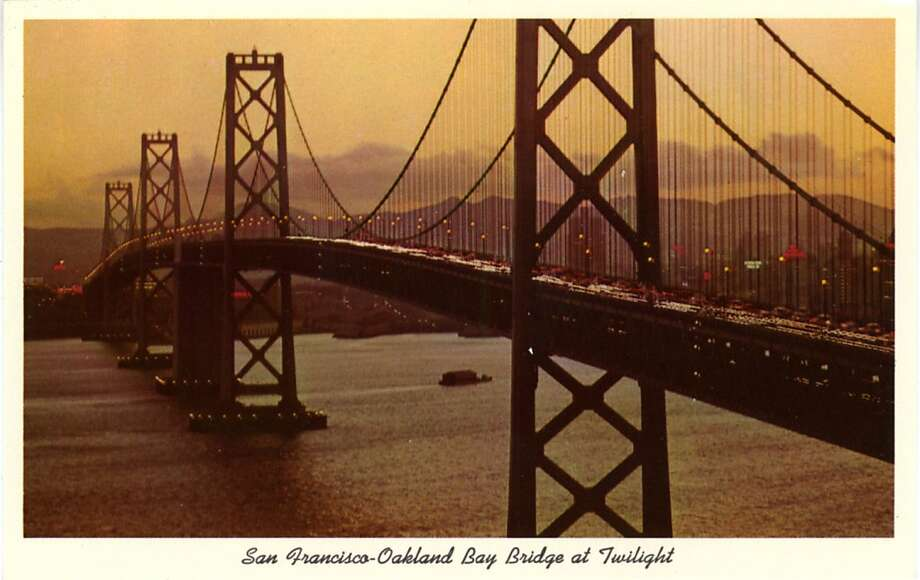 Vintage 1957 postcard showing the San Francisco-Oakland Bay Bridge aglow with twinkling lights as it crosses the bay, the city and mountains are visible in the distance. Photo: Curt Teich Postcard Archives, Getty Images