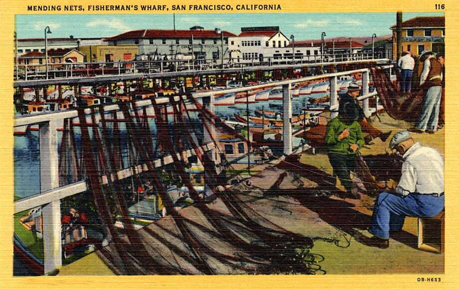 Vintage linen postcard showing fishermen mending their nets on the docks along Fisherman's wharf. Buildings and fishing boast tied to the ocks are visible across the water.  Photo: Curt Teich Postcard Archives
