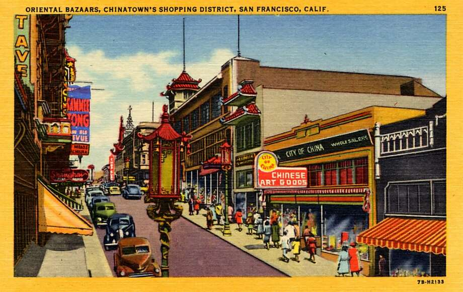 Vintage linen postcard showing a number of stores along a street in Chinatown. Vintage automobiles are parked along the street and pedestrians walk along the sidewalks. Photo: Curt Teich Postcard Archives