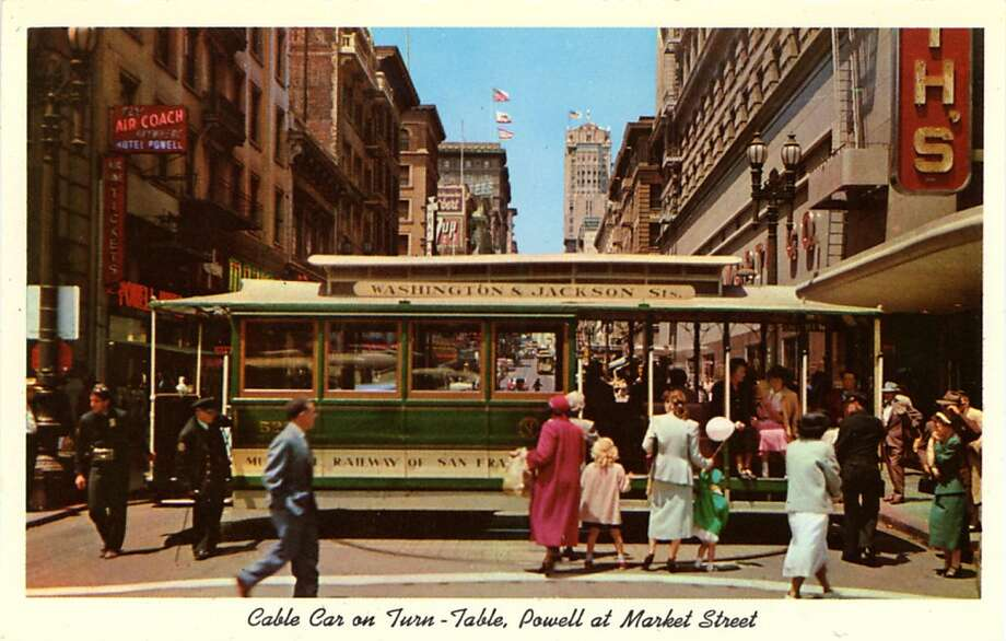 Vintage postcard showing a cable car on the turntable in downtown San Francisco. People wait to embark the car and the cityscape is visible in the background. Photo: Curt Teich Postcard Archives