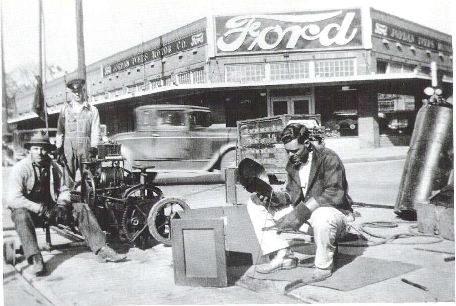 This undated photo shows streetcar repair in front of Jordan-Ivers Motor Co. (now Jordan Ford) with Model A cars visible in the window. Photo: File Photos