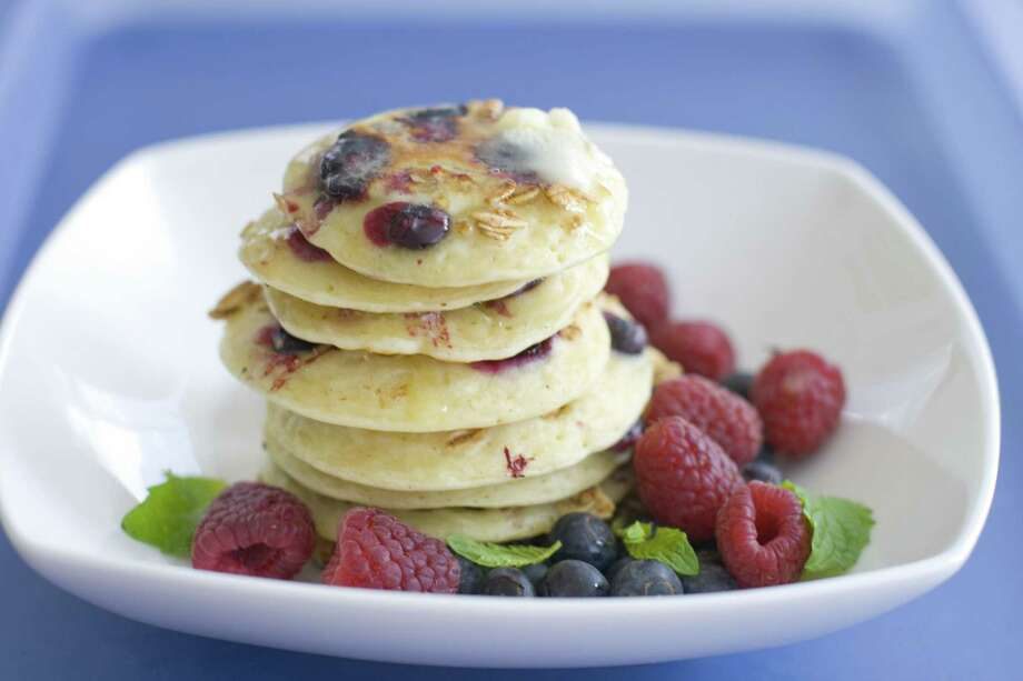 This file photo shows a plate of pancakes with blueberries and granola mixed in the batter. A study of older men found those who regularly skipped breakfast had a 27 percent higher risk of a heart attack than those who ate a morning meal. Photo: AP