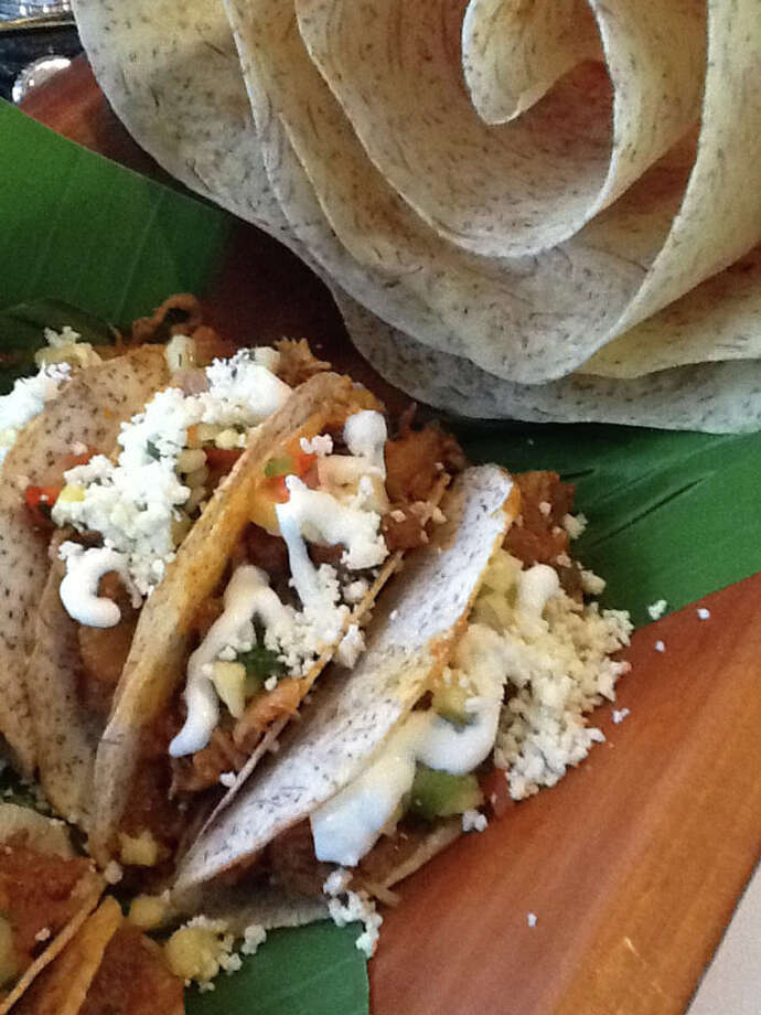 Cordua Catering created pulled pork tacos that used fried thinly sliced malanga root as the taco shell. Photo: Greg Morago, Houston Chronicle