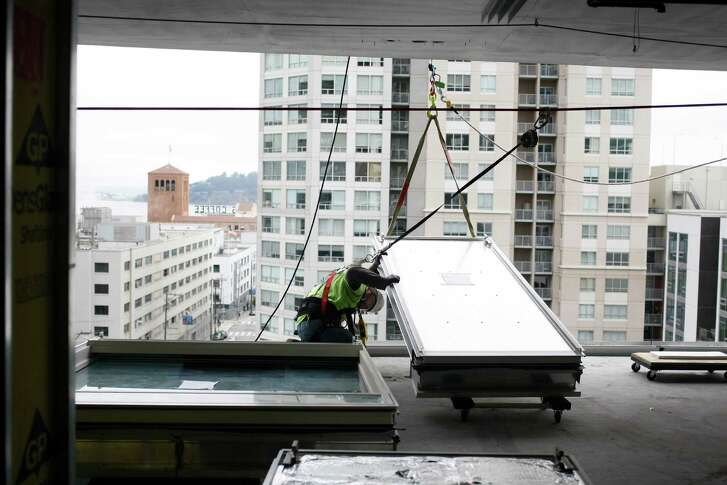 Gerardo Gonzalez works to install an aluminum panel during construction of the One Rincon Hill Phase Two project in San Francisco in 2013.