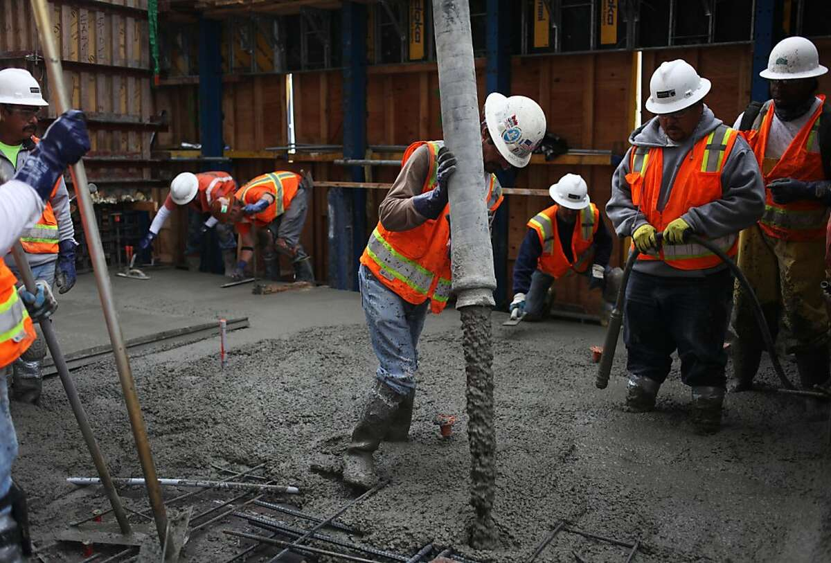 Hilario Venegas, center, pours concrete for the floor of level 34 atop One Rincon Hill Phase Two on July 25, 2013 in San Francisco, Calif.