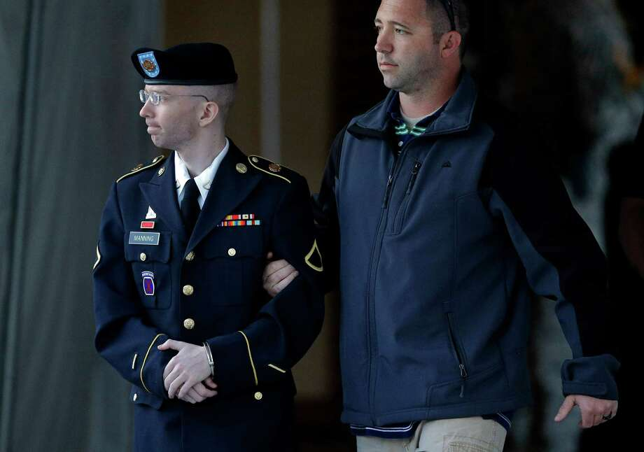 Army Pfc. Bradley Manning, left, is escorted to a security vehicle outside of a courthouse in Fort Meade, Md., Monday, July 29, 2013, after the third day of deliberations in his court martial. Manning faces charges including aiding the enemy, espionage, computer fraud and theft for admittedly sending hundreds of thousands of classified documents and some battlefield video to the anti-secrecy website WikiLeaks while working as an intelligence analyst in Iraq. Photo: Patrick Semansky