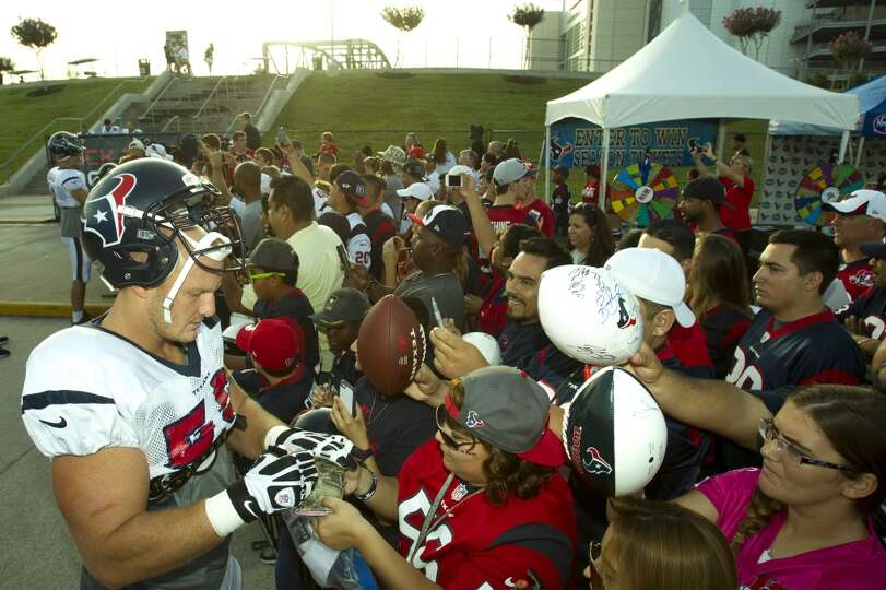 Center Chris Myers (55) signs autographs on his way to practice.