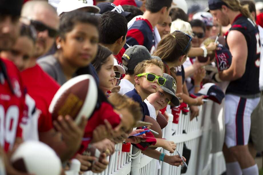Fans line a fence next to the practice field waiting for players to sign autographs. Photo: Brett Coomer, Chronicle