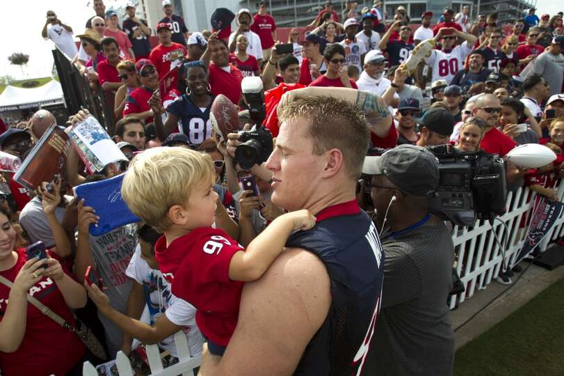 Defensive end J.J. Watt holds 3-year-old Colt Roberds to pose for a photo with him after practice.